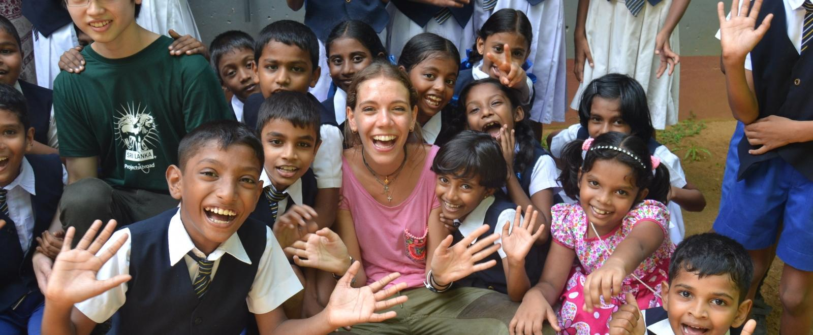A group of children with Projects Abroad Childcare volunteers outside a kindergarten in Sri Lanka.